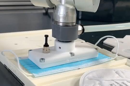 Mini-Flächengreifer greift eine Maske