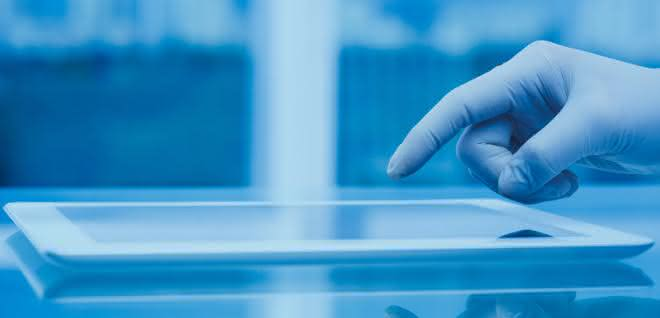 Hand (mit Laborhandschuh) bedient Tablet