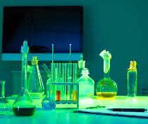 Glaskolben, Reagenzgläser auf einem Tisch und Bildschirm