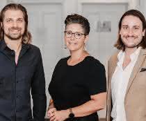 anek Andre (l.) und Benedikt Ruf (r.), begrüßen Nadine Despineux