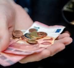 Euro-Scheine und -Münzen in der Hand