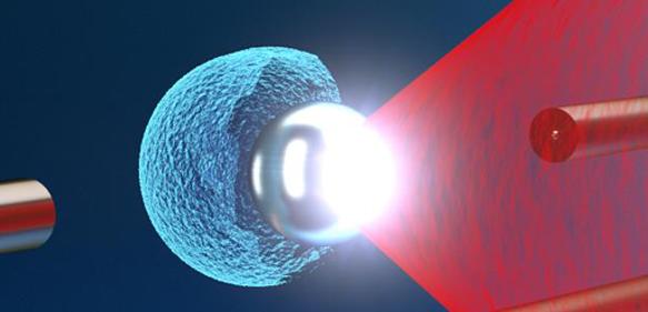 Der Texas Petawatt Laser Puls (rot) wird auf eine schwebende Mikrokugel fokussiert. Die enorme Lichtintensität verursacht die Explosion der Mikrokugel, wodurch potenziell vielseitig nutzbare energetische Ionen (blau) aus einer sehr kleinen Quelle erzeugt werden können. (Bild: Tobias Ostermayr)
